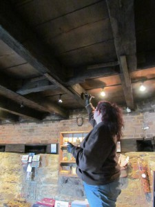 Casey Young of Allegheny Restoration fills cracks in the floor beams with epoxy.  Photo credit - Fort Pitt Society.