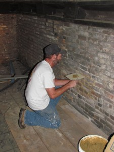 Jim from Mariani & Richards applies new mortar to a section of brick wall in the upper room of the Block House. Photo credit - Fort Pitt Society.